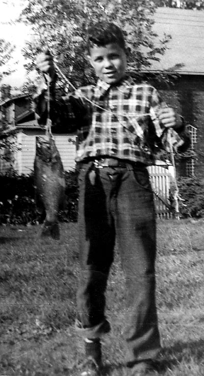 Bob with his first fish, caught in the St. Lawrence River.  Note the lucky rabbit's foot hanging from his belt. (c. 1955)