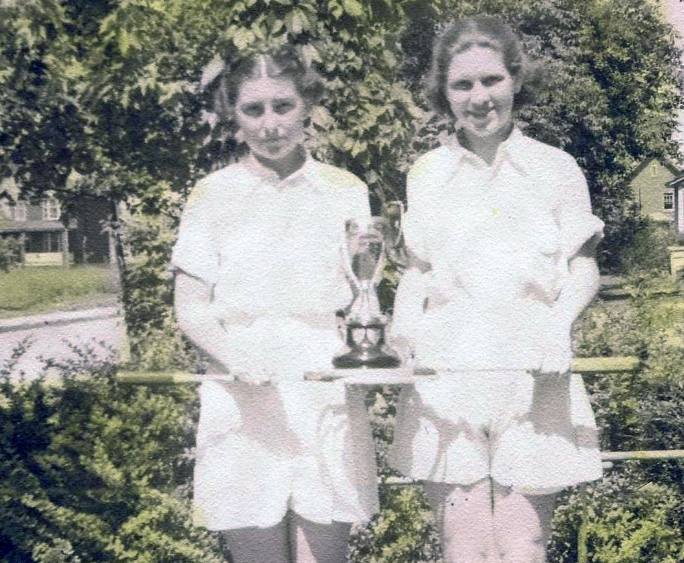 Caption: 1933: Dorothy McNeish (Thomas), SLHS 1939, with unknown friend and tennis trophy in front of Dorothy's house at 328 Maple Ave.